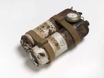 Mixed-media assemblage using rusty propane torch cannisters, cloth straps, wire and a pocketwatch...