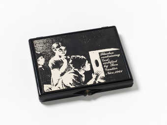 Black plastic box with black and white label printed with line art of children looking into a...