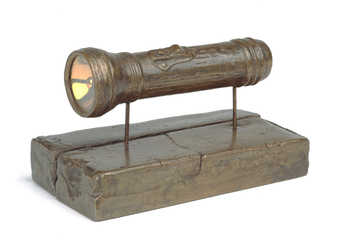 a flashlight cast in bronze, supported on two bronze rods over a small bronze pedestal.  This...