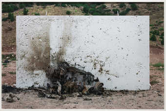 An image of the remnants of a car that has been destroyed by explosives.