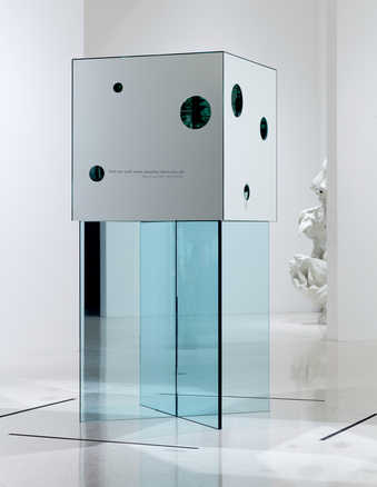 A mirror cube with round access holes cut to the interior exposing a mirror lined interior,...