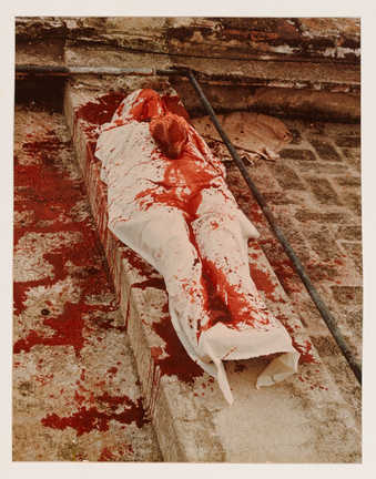 An image of a reclining body, covered with a blood stained shroud.  A cow heart sits on the chest...