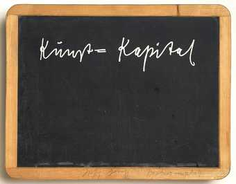 "slate board with white silkscreened text ""Kunst=Kapital"" in wooden frame, with..."