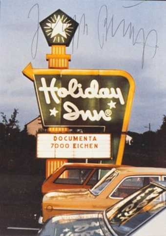 Photo by Staeck/Steidl; image is of a Holiday Inn sign with message board bearing the words...
