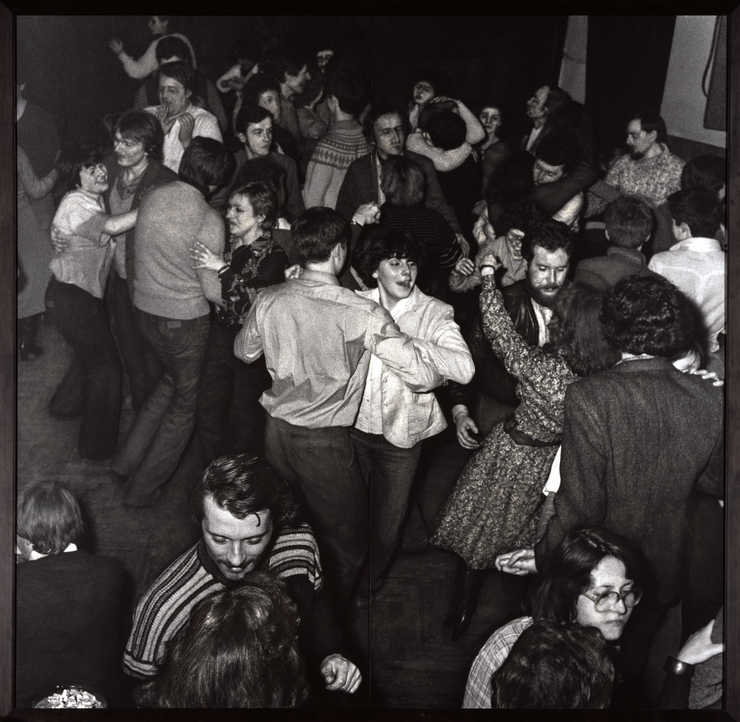 black and white photograph depicting people dancing in a nightclub.