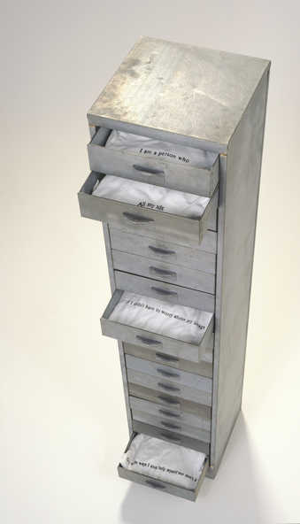 a narrow, tall, cabinet, with 18 drawers.  Each drawer contains a T-shirt with a screen printed...