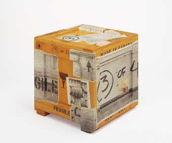A wooden crate with black-and-white photographs stapled to the outside