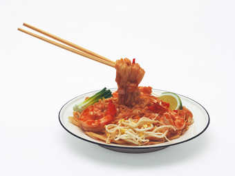 A enameled metal bowl containing  plastic pad thai and wooden chopsticks.  Contact Junko Shimada...