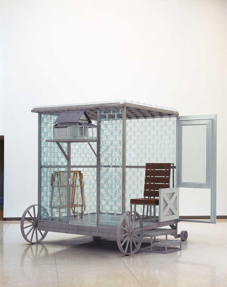 A room on wheels constructed of steel, glass, and plexiglass.  The room is furnished with a...
