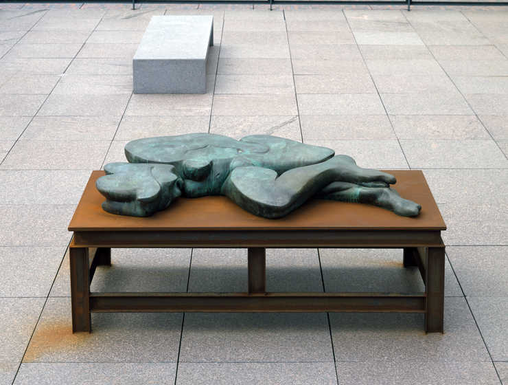 A flattened bronze woman lying on a steel table.