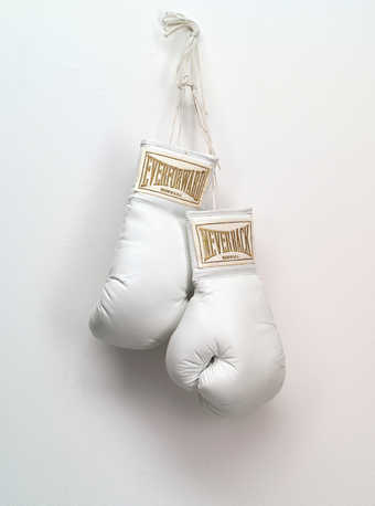 A pair of white boxing gloves with embroidered text on satin pieces on each cuff with the text...