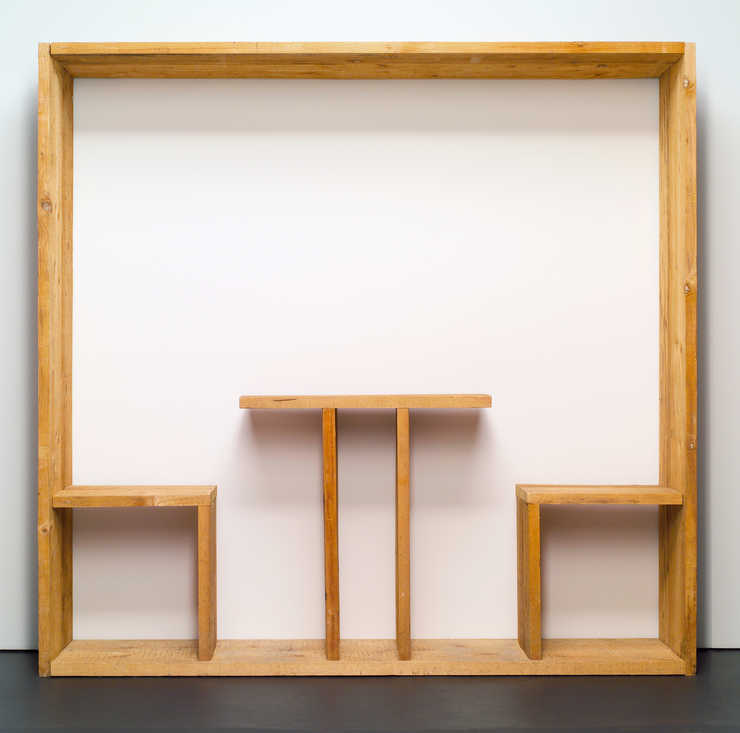 A table and two chairs built within a wooden frame, that is displayed against a wall.