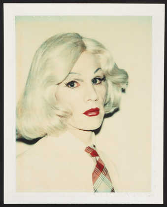 A portrait of Warhol in drag wearing a blonde wig, white shirt and plaid tie.