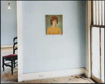 A image of the crumbling interior of an empty residence, with the exception of a painted portrait...