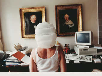 image of the back of a woman from waiste up, with a white bag over her head, sitting at a desk in...