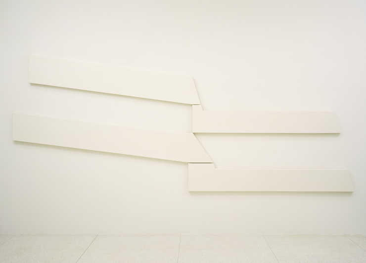 Four white shaped canvases that interlock to create a whole