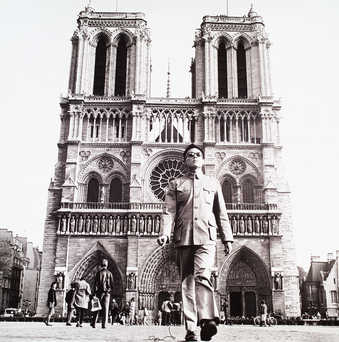 an image of the artist standing in front of Notre Dame Cathedral in Paris