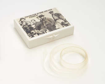 (.1) White plastic box with Maciunas-designed label attached to lid; (.2) contains a  blank 16mm...
