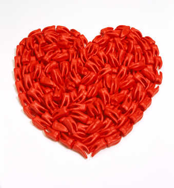 A red paper heart covered with red cast plastic teeth