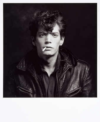 A black-and-white portrait of the artist with a cigarette in his mouth, wearing a leather jacket.
