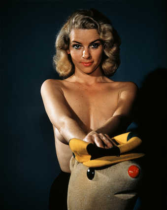 An imabe of a standing shirtless woman, leaning on a toy seal.