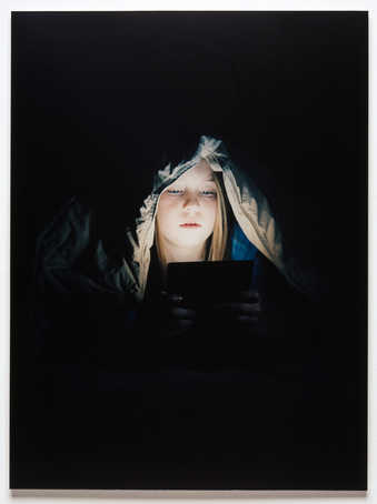 An image of girl with a comforter on her head whose face is illuminated by the electronic device...