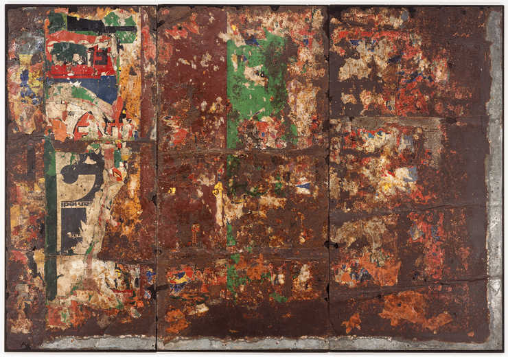 Torn advertisement posters adhered to rusted sheet metal, nailed to wood