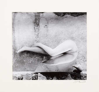 An image of a nude bending at the torso over a mirror.  The model is Ana Mendieta.
