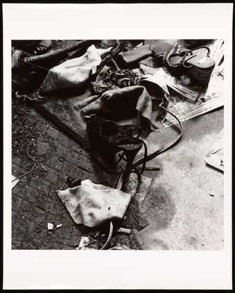 An image of a high-heel shoe amongst street garbage.
