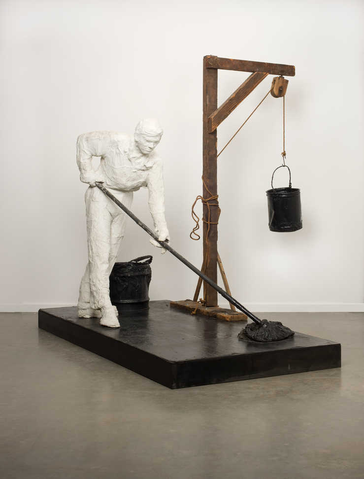A life-size plaster figure holding a mop, seemingly applying tar to a black wooden platform.  To...