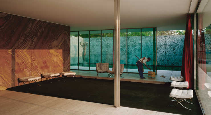 An image of a man cleaning the interior windows of the Van der Rohe Foundation in Barcelona
