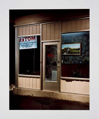 An image of the exterior of a motel lobby with the sign reflected in the window.
