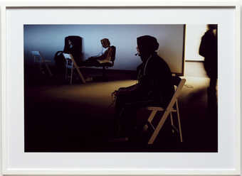 An image of two young men sitting in folding chairs, playing video games.  C-Print on Kodak...