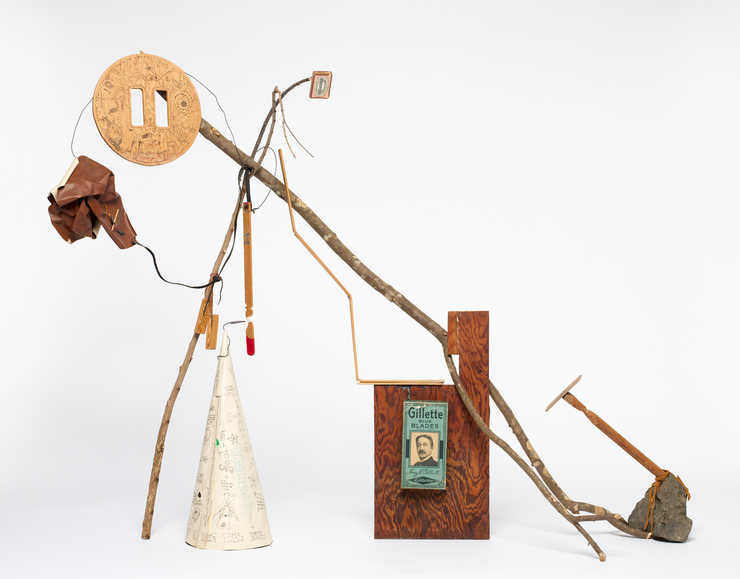 A sculpture comprised of found and artist created objects,  The artist restored the paper dunce...